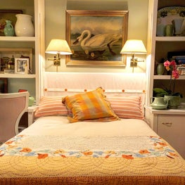 Period guest room with vintage linens and custom headboard