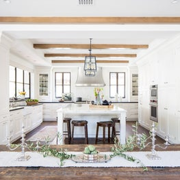 Santa Monica all white classic Spanish kitchen. Exposed beams and wood flooring.