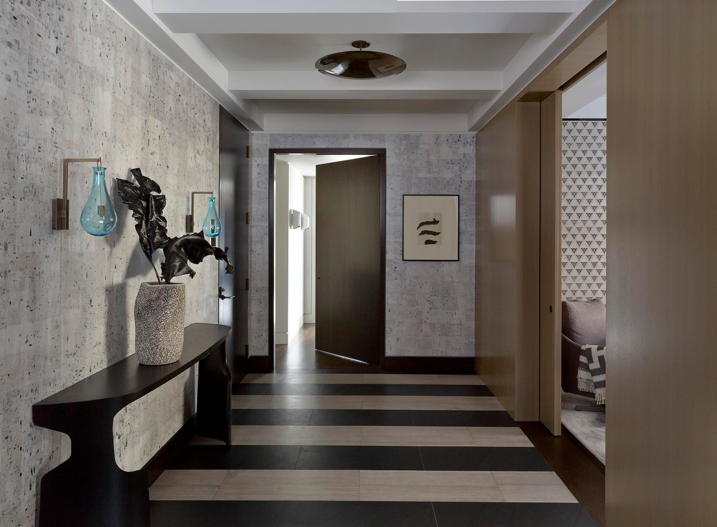 Graphic entrance gallery with custom wallpaper and glass sconces