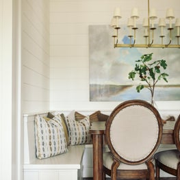 A blend of traditional chairs and built-in seating for a rustic breakfast nook