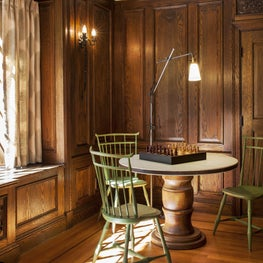 Green windsor chairs; round pedestal table; dark wood paneling; iron floor lamp