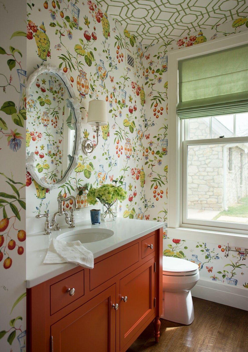 Statement bathroom with floral print wallpaper, burnt orange vanity