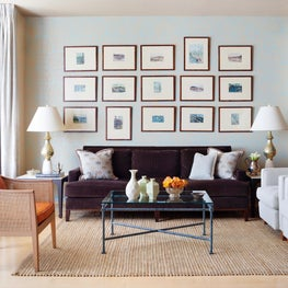 Elegant, eclectic living room with natural rug accent gallery wall, coffee table