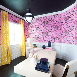 Home office with navy painted ceiling and bold, pink floral wallpaper, plaster medallion