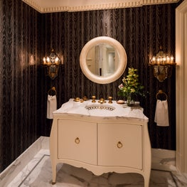 Sleek black wallpaper juxtaposes Carrara marble floors in the powder room.