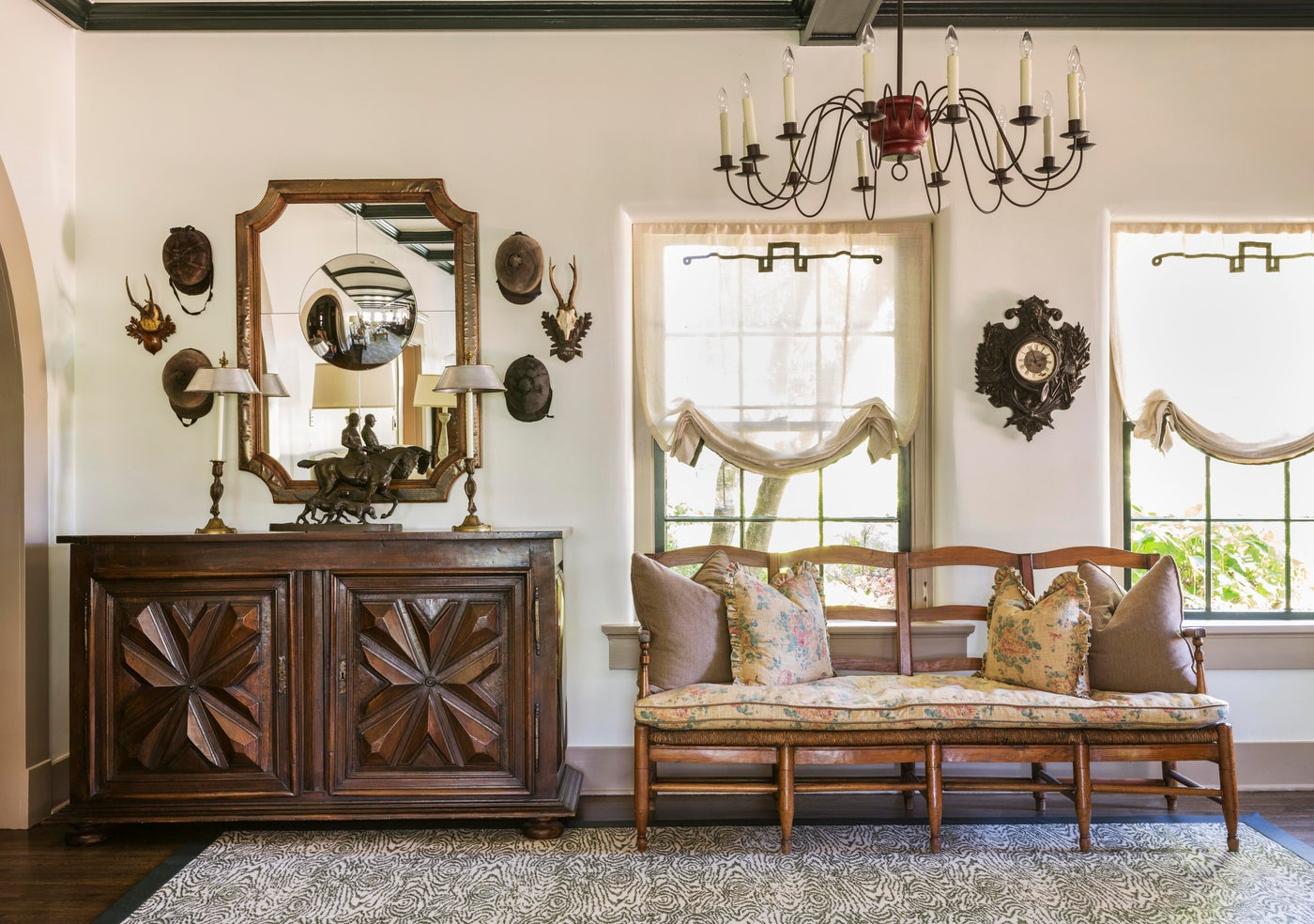 Foyer featuring collection of riding hats and mounts, with an antique bench