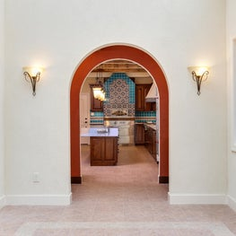 Arched doorways frame the sight line to the colorfully-tiled pizza oven.
