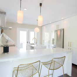 Airy, modern Miami Kitchen features marble surfaces and high-gloss cabinets.