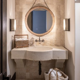 Wall sconces and a round mirror with stone sink complete this powder bath