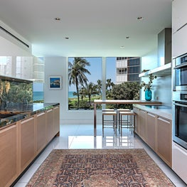 Contemporary Kitchen with two tone cabinets, colorful marble, and silk rug