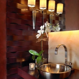 This powder room has woven mahogany wood walls and stainless steel vessel sink.