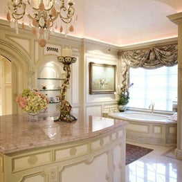 Awash in tones of cream and rose, the room is topped with a ceiling of blush-colored Venetian plaster and decked with a gleaming floor of inlaid rose quartz circles.