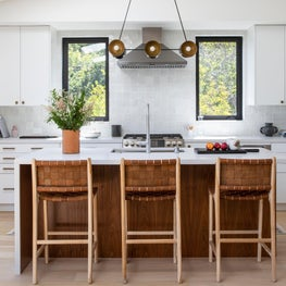 Kitchen with woven leather bar stools, white square tile backsplash, and white cabinets