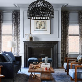 Warm and sophisticated soft blue living room with wooden armchairs