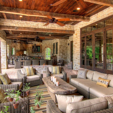 The loggia is a favorite spot for alfresco entertaining. The wine barrel-stave chandelier is a nod to the clients' affection for fine wines, and the old-wagon-wheel barstools bring a little piece of Texas to the scene.
