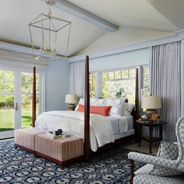 Four poster bed on navy oriental rug, blue checked settee, lantern lighting