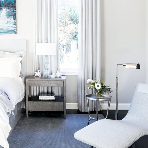 Bright master bedroom with dark-stained wood floors, pops of blue