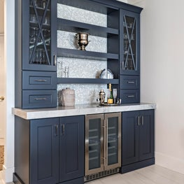 This Custom hale navy bar evokes coastal design and has the perfect mother of pearl backsplash tile.