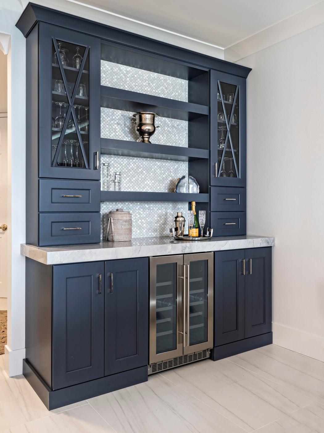 This Custom hale navy bar evokes coastal design and has the perfect mother of pearl backsplash tile.