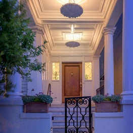 Elegant uplighting highlights detailing of this restored entry porch
