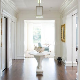 The entryway to the home feels bright and airy thanks to high ceilings and bright white walls.