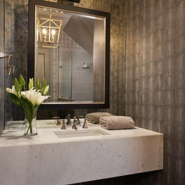 Metallic neutral wallcovering with assorted metal finishes in this updated powder room.