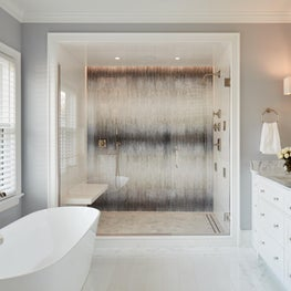 Master, large shower, floating bench, glass mosaic wall, marble floor/counters