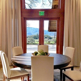 Elegant curtains frame the view of the vinyards from this wine tasting room.