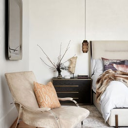 Warm and cozy primary bedroom with plaster walls, hanging pendant lights, and a gold mirror