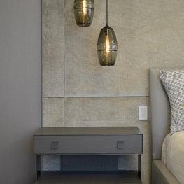 A Pair of Pendant Lights Hang Above a Carol Kurth Designed Nightstand