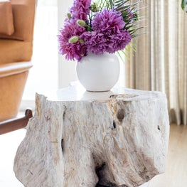 Beautiful pink dahlias pair with pygmy date palm (phoenix roebelenii) leaves in a handmade ceramic vessel atop a one of a kind petrified wood side table.