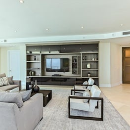 Neutral living room with builtin tv cabinet and shelves; modern twin arm chairs.