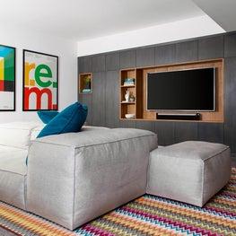 Modern basement TV room with sleek wall of built-ins