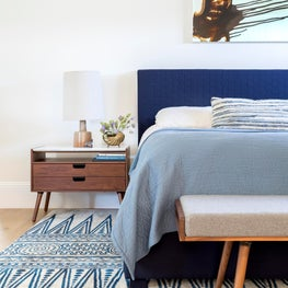 The bespoke upholstered bed was custom quilted in a honeycomb pattern to add depth and dimension to the serene palette. Marble tops on the handmade Walnut nightstands ensure a low-maintenance space. Above the bed, an abstract painting by Ruben Vincent.