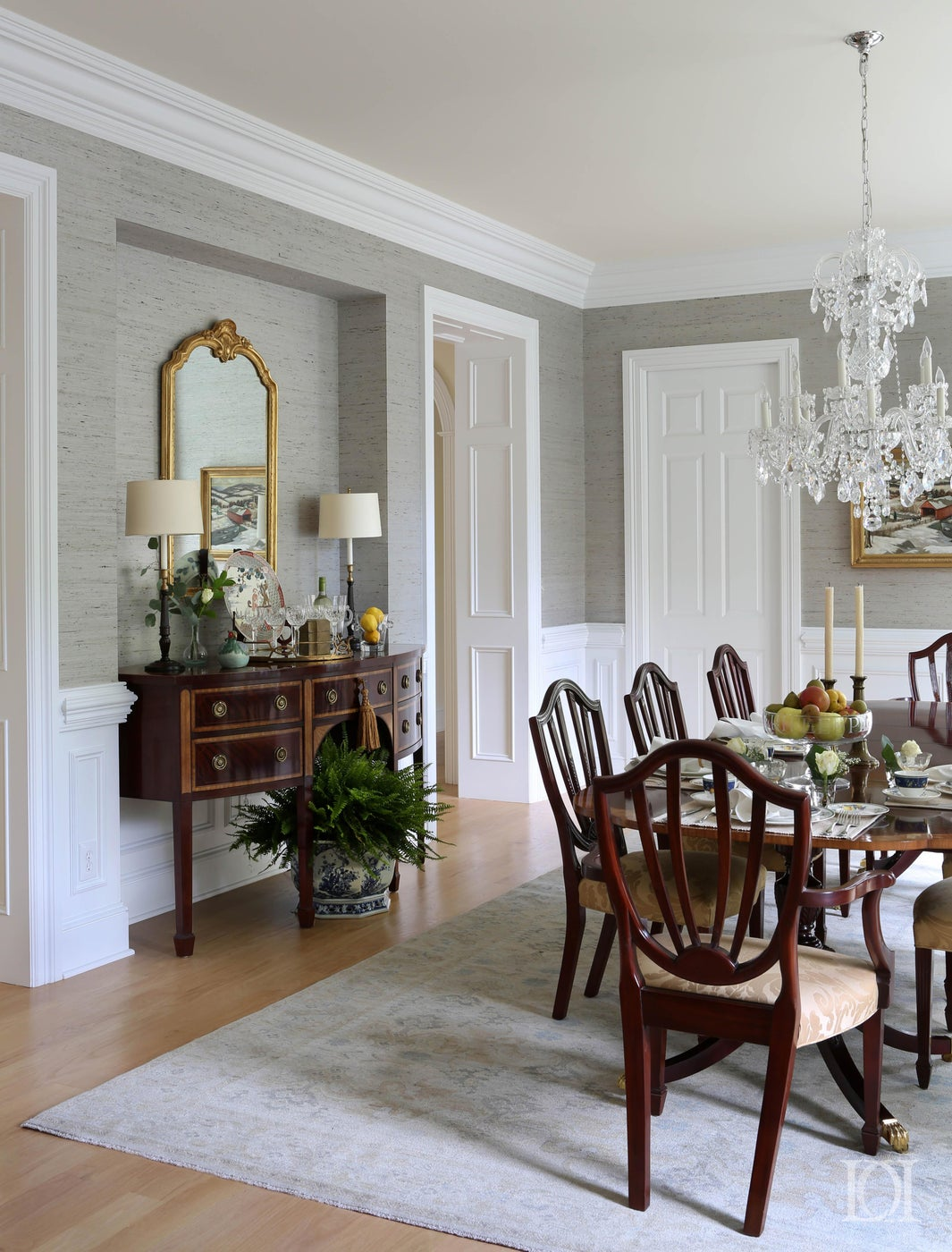 Dining Room with oriental rug, crystal chandelier and grass cloth wallpaper