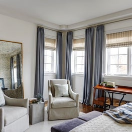 Master bedroom with blue wool drapes, cream walls, gray chairs & desk