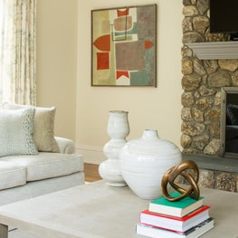 Modern Art by Stanley Bate and transitional linen wrapped coffee table combined with more traditional furnishings make this family room fresh and inviting.