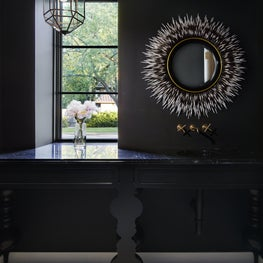 This powder room goes glam with high end finishes and unique vanity details