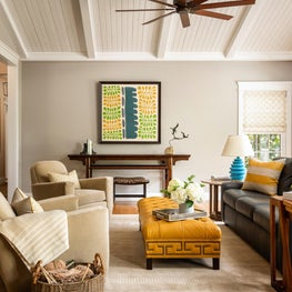 Modern Family Room with mustard leather colored ottoman, suede club swivel chairs, altar table