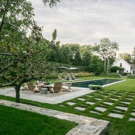 A fruit orchard sits behind the firepit terrace, transitioning to the pool house