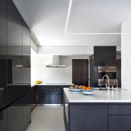 Minimal kitchen with Bulthup cabinetry and stone floors.