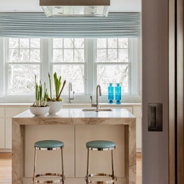 Wellesley Family Home, Kitchen island with marble countertops that waterfall
