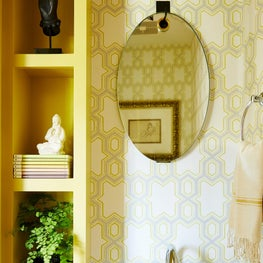 3/4 Bathroom with geometric patterned wallpaper and built-in shelving. Pedestal sink