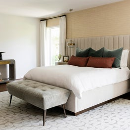 Neutral-toned master bedroom with a bench and grey console