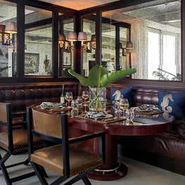 French Bistro-Inspired Leather Banquette Dining Area with Antiqued Mirror Panels