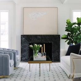 Inviting living room with montauk sofa, custom swivel chairs, rug company rug, and custom marble fireplace surround.