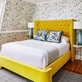 Coastal bedroom with Romo wallcovering and punchy yellow