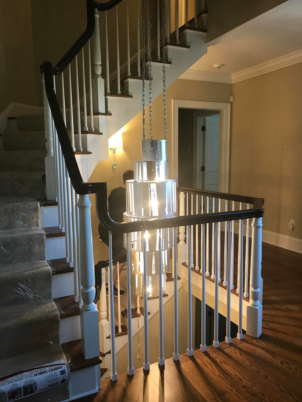 Staircase with hanging center pendant, traditional railings