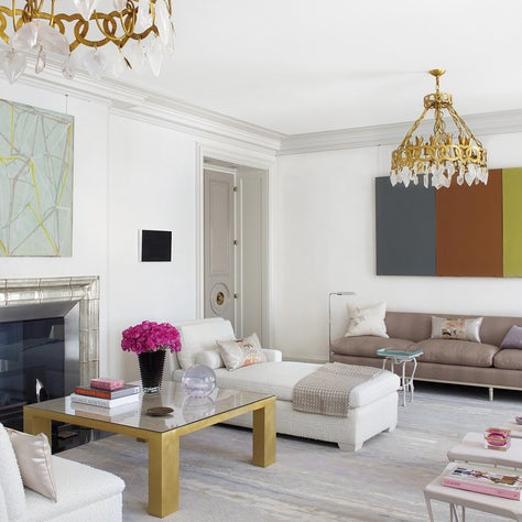 Low furniture and monochromatic paint in living room draw attention to the art; mantel in poured mercury glass