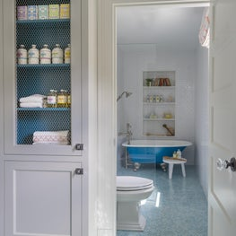 Bathroom with Build in Shelves and Blue Claw Foot Tub